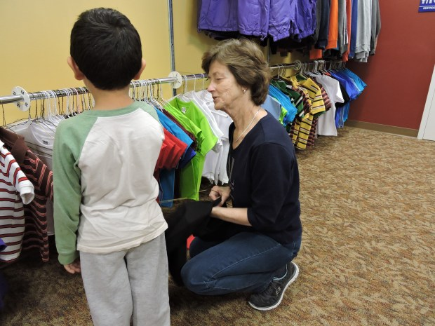 Assistance League member Penny Smith helps student select shirts in Operation School Bell. (Photo courtesy of Assistance League)