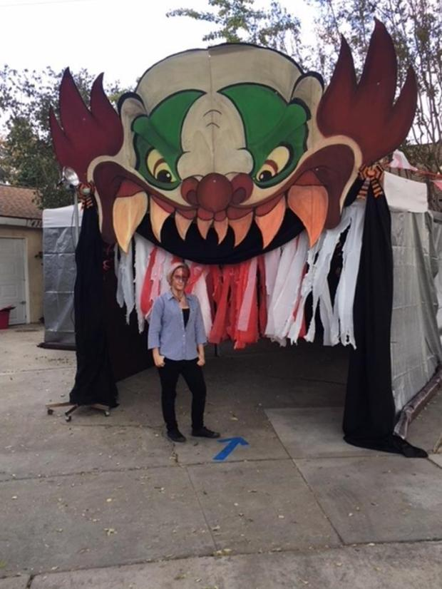 Zena Bengtson, 15, of Riverside, stands next to her creation, an 18-foot high game booth for trick-or-treaters on Halloween. The artwork had formerly been a refrigerator box. (Photo courtesy of Jim Bengtson)