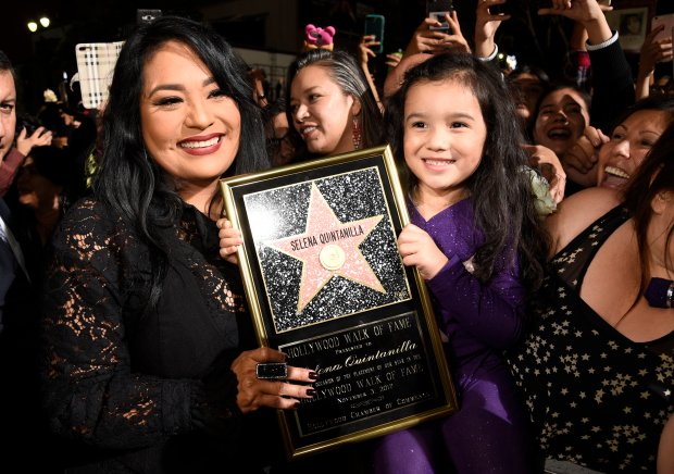Suzette Quintanilla, left, sister of the late singer Selena Quintanilla, holds a replica of her sister's star on the Hollywood Walk of Fame as she poses with young fan Sammi Corona-Lampa, 4, of Moreno Valley, Calif., following a posthumous star ceremony for Selena on Friday, Nov. 3, 2017, in Los Angeles. (Photo by Chris Pizzello/Invision/AP)