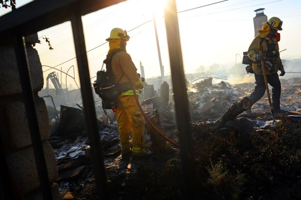 Firefighters put out hotspots after a home burned in the Thomas Fire near Ventura, CA.(Photo by Andy Holzman/SCNG)