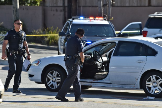 Torrance police officers inspect vehicle in parking lot adjacent to the YMCA on Sepulveda Blvd where a mans body was found Thursday afternoon. The man was pronounced dead at local hospital. Police are investigating. Photo by Robert Casillas, Daily Breeze/SCNG