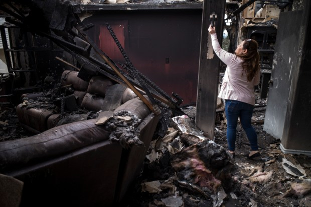 Maria Hernandez retrieves a cross from her destroyed home on Gavina Avenue in Sylmar Sunday, December 10, 2017. Hernandez's home was burned in the Creek fire which roared through the Sylmar neighborhood early Tuesday morning. On Sunday she and her husband returned to see what remained of their home of 14 years. (Photo by David Crane/Los Angeles Daily News-SCNG)