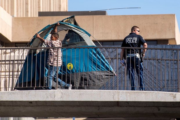 With Santa Ana police officers supervising, a homeless man carries his tent across the bridge between the Plaza of the Flags and the law library building in Santa Ana on Wednesday, December 13, 2017. People had been asked to move from the plaza so that the area could be power washed. (Photo by Paul Rodriguez, Orange County Register/SCNG)