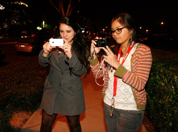 Julia Fees, left, and Pia Dizon take photos for their Facebook accounts of cars lining up to enter Disneyland. (File photo by Armando Brown, Orange County Register/SCNG)///ADDITIONAL INFO: 01.n.disney.leapday.line.02xx.ab - shot 02/28/12 - ARMANDO BROWN, FOR THE ORANGE COUNTY REGISTER - Folks line up Tuesday night to enter Disneyland on Wednesday morning.