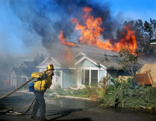 A LAFD firefighter carries dry hoselines up the street and past a burning house in the Santiago Estates area of Sylmar during the Creek fire on Dec. 5, 2017. (Photo by Mike Meadows)