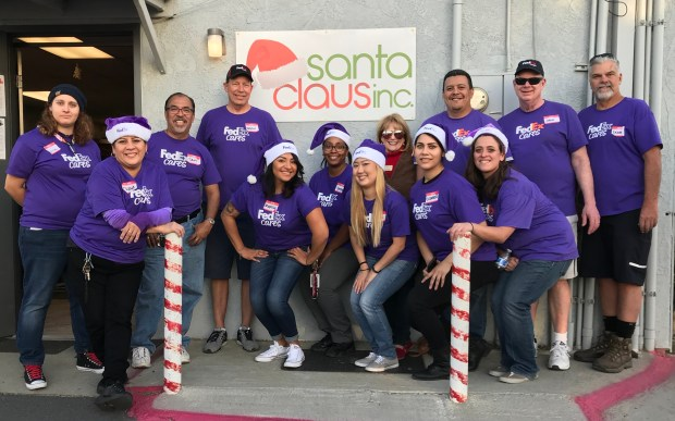 Volunteers from FedEx work with Karen DiCarlo of Santa Claus Inc. at the nonprofit's San Bernardino warehouse.Courtesy photo