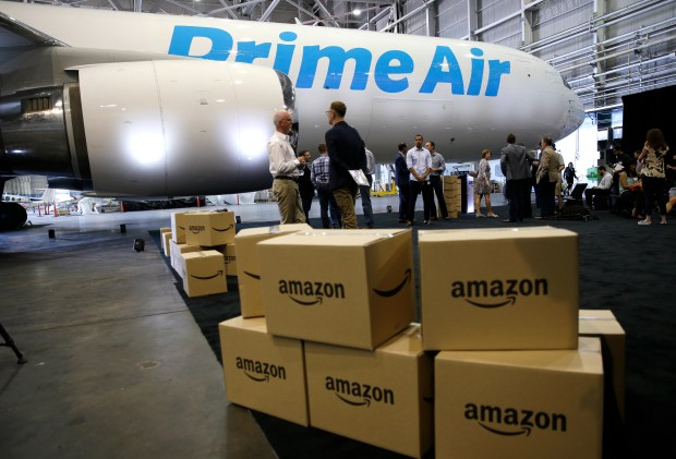 """FILE - In this Thursday, Aug. 4, 2016, file photo, Amazon.com boxes are shown stacked near a Boeing 767 Amazon """"Prime Air"""" cargo plane on display in a Boeing hangar in Seattle. With Christmas 2017 on a Monday, most retailers have one less day to get packages delivered on time. Retailers have been trying to speed up delivery as they try to replicate the service offered by Amazon. (AP Photo/Ted S. Warren, File)"""