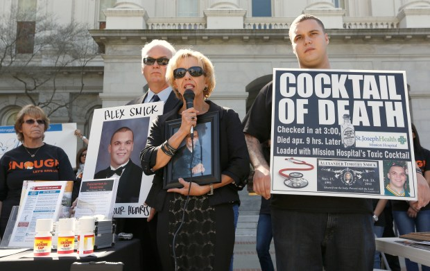 Tammy Smick, center, flanked by her husband, Tim left, and son, Chris, called on the Medical Board of California to crack down on doctors whose overprescribing of medications has led to death or serious injuries during a rally at the Capitol in Sacramento in 2013. The Smicks, whose other son, Alexander, died after an overdose of a drug prescribed by a doctor, were among several families that testified before s joint legislative committee looking into whether to reauthorize the physician-run board. (AP Photo/Rich Pedroncelli)