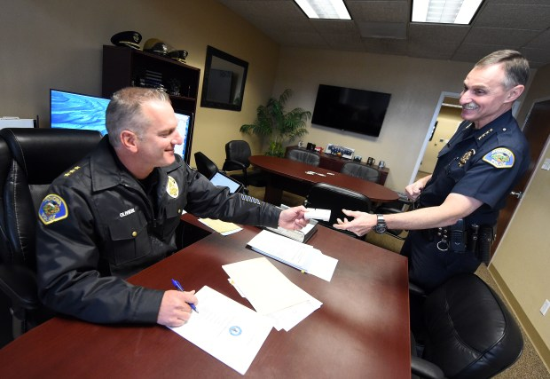 Pomona Police Chief Paul Capraro (right) hands over his freeway transponder to interim Pomona police chief Mike Olivieri Monday. Capraro is retiring Tuesday December 19, 2017 after serving 30 years on the force. (Photo by Will Lester-Inland Valley Daily Bulletin/SCNG)