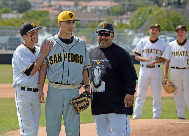 San Pedro High baseball player Evan Jimenez, center, made a surprise appearance to throw out the first pitch before a junior varsity game against Banning Tuesday, April 25, 2017, San Pedro. Jimenez was severely beaten in a gang attack.(Photo by Steve McCrank, Daily Breeze/SCNG)