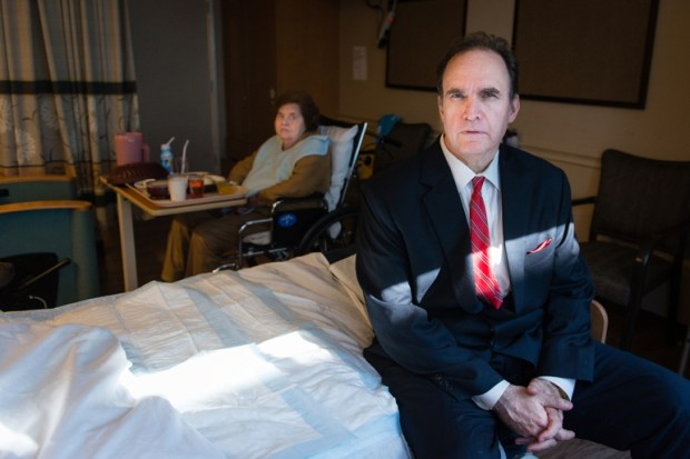 """James Morris visits his mother, Georgina Morris, on Nov. 14, 2017. Morris said he was disturbed by the unsanitary practices he saw at his mother's nursing home. """"Workers were coming in and out without washing their hands,"""" he says. (Heidi de Marco/KHN)"""