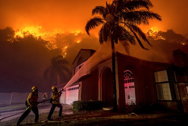 Firefighters battle to save homes as the Canyon Fire 1 burns on San Ramon Drive in Corona on Sept. 25, 2017. Cal Fire/Riverside County Fire Chief John Hawkins said those living in residential neighborhoods near wildland areas should anticipate more of these fires in 2018 and should be ready to evacuate at a moment's notice.File photo by Watchara Phomicinda/The Press-Enterprise/SCNG