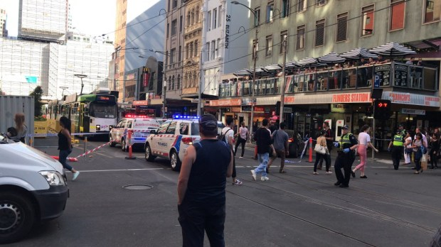 Pedestrians walk past as police and emergency services attend the scene of an incident involving a vehicle and pedestrians in Melbourne, Thursday, Dec. 21, 2017. Police have arrested a driver after a car drove into pedestrians on a sidewalk in central Melbourne. (Kaitlyn Offer/AAP Image via AP)