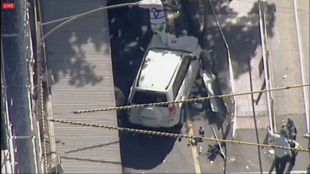 In this photo made video from the Australian Broadcasting Corp., a white SUV vehicle is stopped after allegedly striking pedestrians, Thursday, Dec. 21, 20217, in Melbourne, Australia. Local media say over a dozen people have been injured after a car drove into pedestrians on a sidewalk in central Melbourne. (Australian Broadcast Corp. via AP)