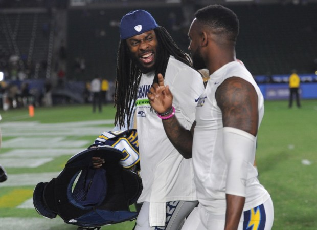 Chargers cornerback Casey Hayward, right, shares a laugh with Seattle cornerback Richard Sherman after the two exchanged jerseys following an exhibition game at the StubHub Center in Carson on July 13. (Photo by Stephen Carr / SCNG )
