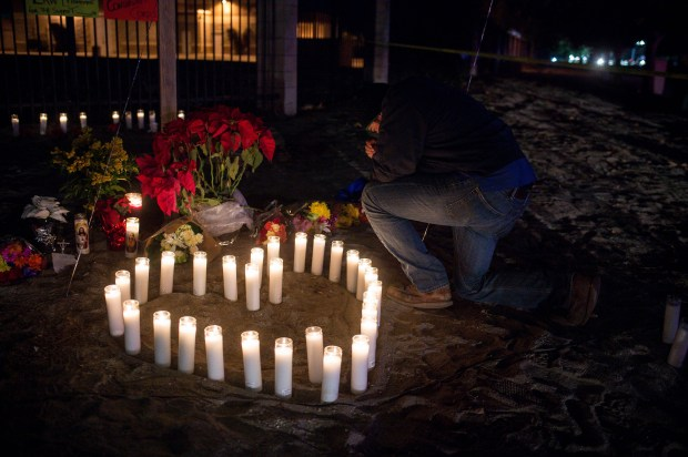 Aaron Fierro prays and leaves a candle, Thursday December 3, 2015 at a makeshift memorial to the 14 people killed and 22 injured during the December 2 mass shooting at the Inland Regional Center in San Bernardino, California. (Staff file photo, The Sun/SCNG)
