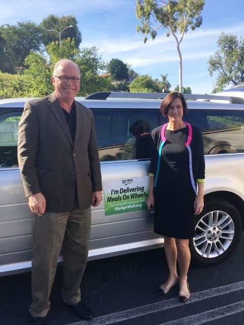Age Well Senior Services Acting CEO Steve Moyer, left, and Rep. Mimi Walters stand beside a Meals on Wheels delivery vehicle. (Courtesy of Age Well Senior Services)