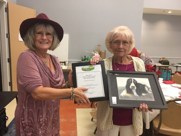 "Murrieta GEM of the Valley Art Association president Cathy Baca, left, presented the group's 2017 blue ribbon to Joy Pari for her watercolor painting ""Charlie Cat"" in December 2017. (Photo courtesy of Murrieta GEM of the Valley Art Association)"