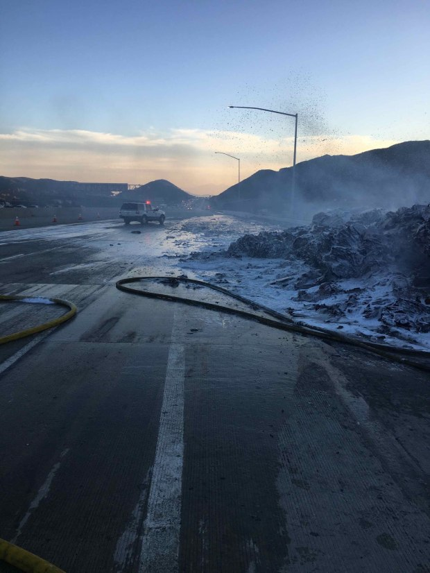 Firefighters work to clean up a mound of burned cardboard from the side of the southbound 15 Freeway near the Glen Helen Parkway exit in Devore on Tuesday, Dec. 5, 2017. A flatbed trailer loaded with bundled cardboard caught fire Tuesday afternoon, sending flaming paper rolling downhill that ended up burning a couple of acres of vegetation. (Photo courtesy of San Bernardin