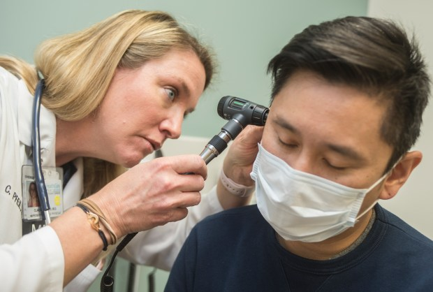 Claudia Pfeil, MD, examines Charles Lin, of Alhambra, who has the flu symptoms at Pasadena Urgent Care Health Care Partners in Pasadena Friday, January 5 2018. A mighty wave of flu has gripped the nation and Southern California. LA County is seeing widespread influenza which means emergency rooms and urgent cares are packed. (Photo by Walt Mancini/Pasadena Star-News/SCNG)