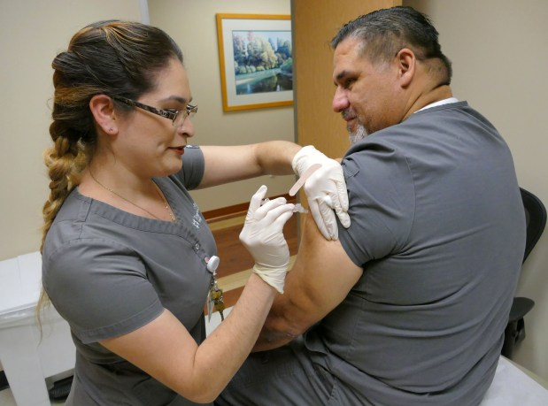 A wave of flu has gripped Southern California as the virus is now widespread, overwhelming hospitals and urgent care centers earlier in the season than usual. Medical assistant Ingrid Rios gives a flu shot to Mario Pineda at Torrance Memorial Primary Care Center in Torrance. Photo by Robert Casillas, Daily Breeze/SCNG
