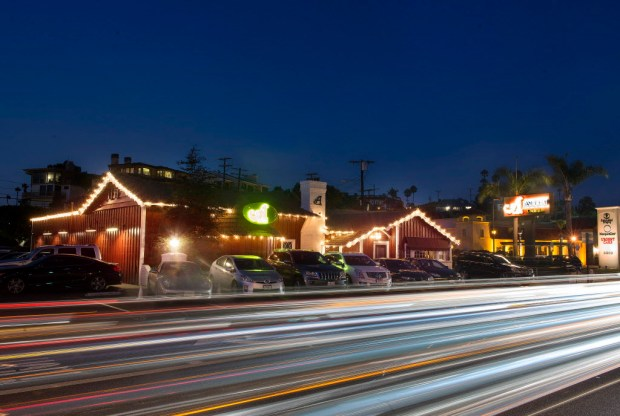 Traffic along W. Coast Hwy. at Newport Beach Blvd glows against Newport Beach's A Restaurant and A Market. A revamp in 2007 renamed it A Restaurant. ///ADDITIONAL INFORMATION: FOOD.BeenThere.ARestaurant.cy 08/09/16 Ð CINDY YAMANAKA, ORANGE COUNTY REGISTER Newport Beach- not a review but a profile of the restaurant for the Been There Forever column. Story talks about this longtime OC favorite and changes it has been through, it's the former Arches and has a long history and was a celeb hangout in the Golden Age of Hollywood with guests from the Rat Pack to Shirley Temple and John Wayne. A revamp in 2007 with a partnership led by movie producer/director Joseph McGinty Nichol, aka McG, renamed it A Restaurant. Decor was not changed dramatically, it still has dark wood and red interior with B&W photos.