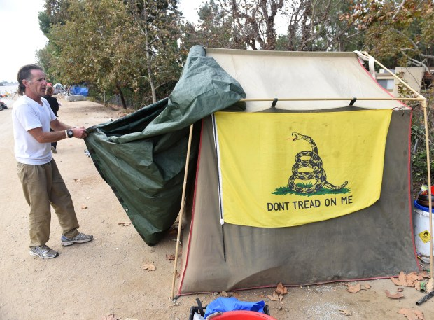 Larry Ford dismantles his tent along the Santa Ana Riverbed in Foutain Valley. He moved his tent to the Honda Center encampment. (Photo by Bill Alkofer, Orange County Register/SCNG)