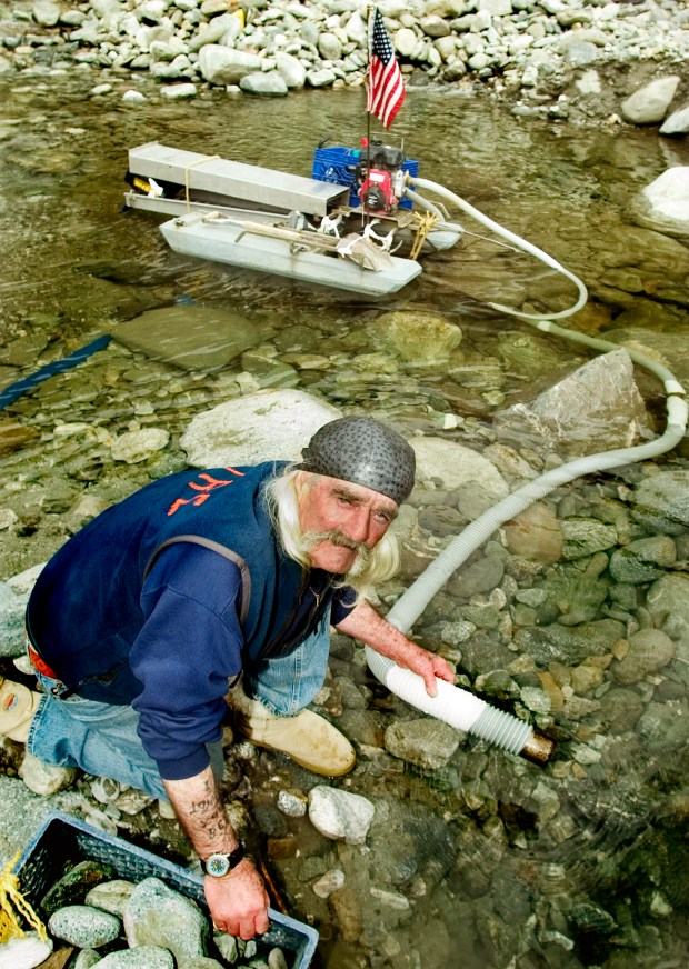 """Bernie McGrath pictured in 2007 with dredge equipment in the East Fork River. McGrath was one of the few remaining gold miners in the San Gabriel Mountains. He used to volunteer as """"the eyes of the mountain"""", for the East Fork volunteer fire department. (SGVN/Photo by Walt Mancini/SVCity)"""