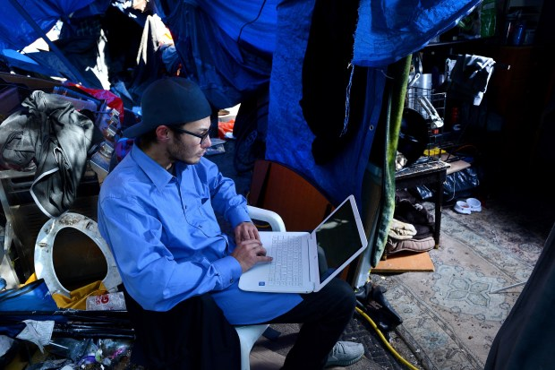 Nick Trullench works on his laptop in a friend's tent. Trullench is a former Geek Squad technician. He lost his job not long after he found out that he has Crohn's disease. He's been homeless on the riverbed since July,2015. He said he is on the waiting list to receive a Section 8 housing voucher but doesn't have faith he'll receive one. He predicts he'll end up on the streets of Orange or Anaheim when he leaves the encampment. (Photo by Bill Alkofer, Orange County Register/SCNG)