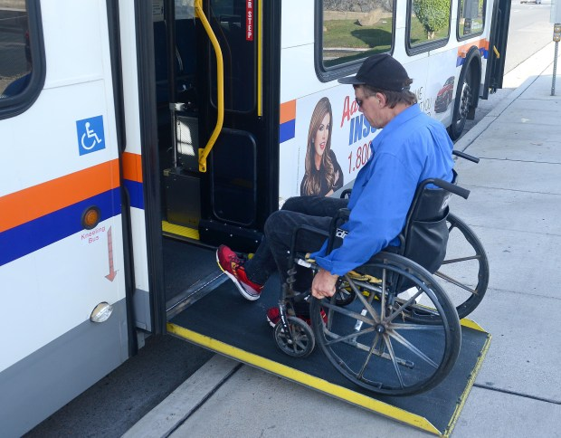 James Petkus gets on the bus enroute to a court appearance. He was ticketed for illegal camping. Petkus has been in a wheelchair since he had an accident while working as a roofer. He's suffering from injured discs and nerve damage. He uses heroin to numb the pain. (Photo by Bill Alkofer, Orange County Register/SCNG)