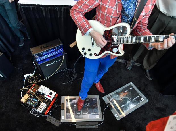 Loki Davison, director of Poly Expressive, shows plays guitar as he shows off their MIDI Foot Controller during a media preview at NAMM in Anaheim, California, on Wednesday, January 24, 2018. (Photo by Jeff Gritchen, Orange County Register/SCNG)