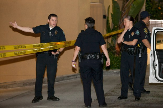 Irvine police officers investigate after Monica Quan and Keith Lawrence were found shot to death in a parking garage in Irvine in 2013. (Photo by KEVIN WARN, Contributing photographer)