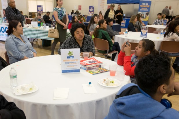At an Anaheim tax preparation fair, table signs encourage workers to claim earned income tax credits. EITCs offer cash back to minimum wage workers even when they earn too little to pay income tax. (Photo by David Kawashima/Orange County United Way)