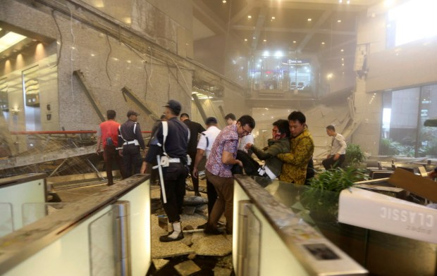 An injured man is carried out of the Jakarta Stock Exchange tower after a floor collapse in Jakarta, Indonesia, Monday, Jan. 15, 2018. A mezzanine floor inside the tower collapsed on Monday, injuring dozens of people and forcing a chaotic evacuation. (AP Photo)