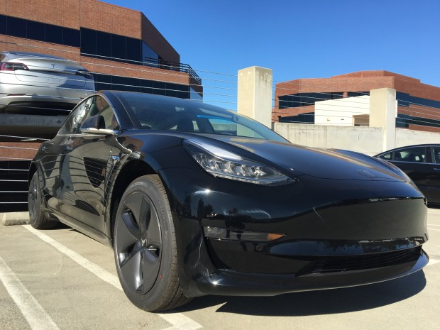 A Tesla Model 3 is parked behind an office building in Costa Mesa. (Photo by Penny Arevalo, SCNG)