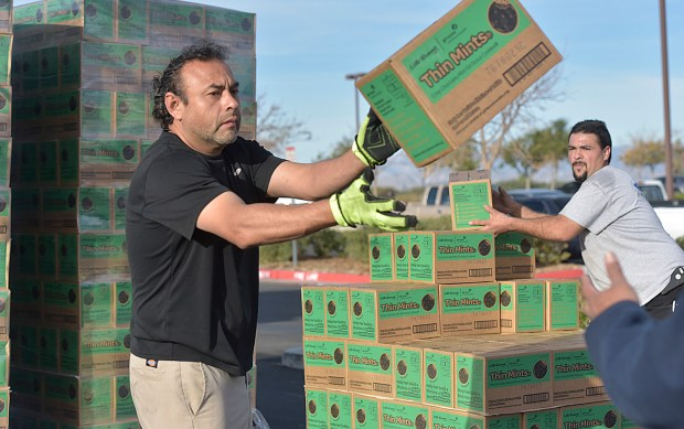 Rene Nunez, left, and Hector Del Villian toss cases of Girl Scout cookies Saturday, Jan. 27, 2018, at a Babies-R-Us parking lot in Santa Clarita, where more than 200 volunteers distributed more than 17,000 cases of cookies for the Scouts' annual cookie fundraiser. Photo by Dan Watson, Contributing Photographer