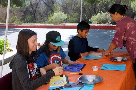 Sewing and craft expert Cynthia Duran helps Angel Tree youth create stories and book covers using decoupage and fabric scraps. She will lead crafts at Community Outreach Ministry's Valentine Celebration on Feb. 10, 2018. (Photo courtesy of Community Outreach Ministry)