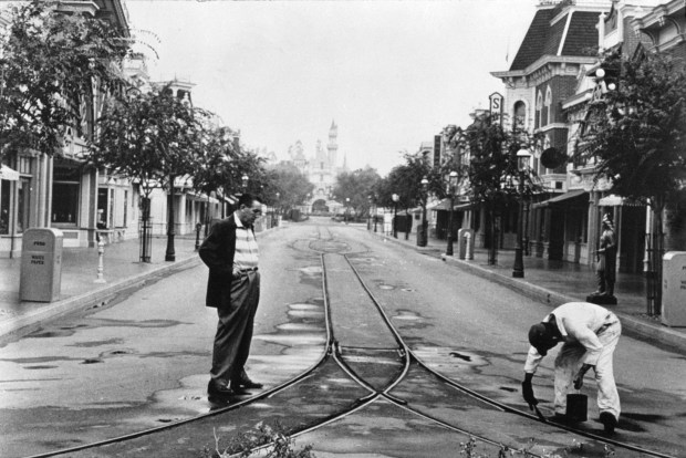 Walt Disney looks over finishing touches to the streetcar tracks on Main Street shortly before Disneyland opens. Photo courtesy of Disneyland Park.