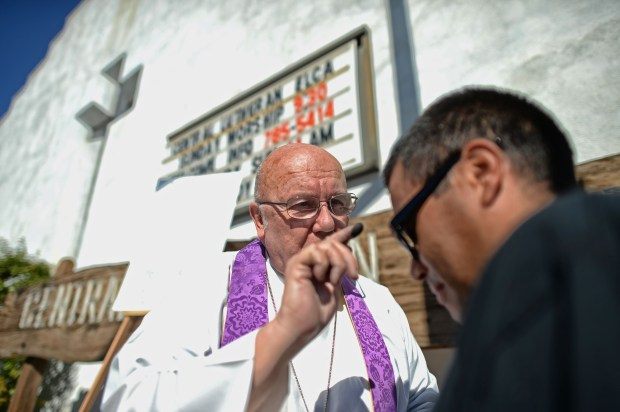 The Rev. Larry C. Eckholm places ashes on the forehead of Martin Espino, 31-years-old, Homeless, as symbol to those readying themselves to participate in the season of Lent, outside the Central Lutheran Church at Tyrone Avenue and Victory Boulevard, in Van Nuys, Wednesday, February 10, 2016. (Photo by Hans Gutknecht/Los Angeles Daily News)