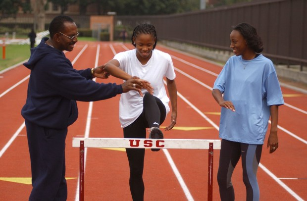 Charles Leathers works with Gayle Hunter (center) and Ashlee Brown during the 2003 track and field season. (Kirby Lee/The Sporting Image)