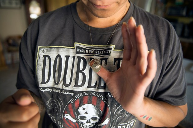 Monique Lang wears her husband's wedding ring around her neck. They met when she was still in high school. She said he was an outgoing and funny 19-year-old, with beautiful green eyes and a sharp wit. (Brian Rinker for California Healthline)