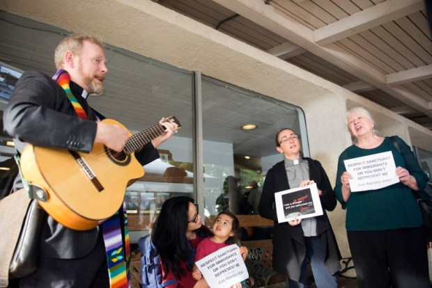 People opposing sing while playing guitar before a hearing on an ordinance to exempt Los Alamitos from the California Values Act law that limits cooperation between local law enforcement and federal immigration authorities on Monday, March 19, 2018. (Photo by Matt Masin, Contributing Photographer)