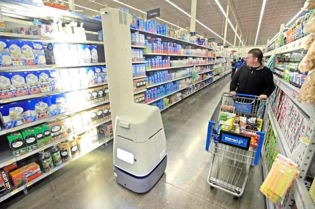 Shopper Gerry Scott, right, watches as the Bossanova robot scans shelves containing trash bags at Walmart in Burbank. The company is testing the shelf-scanning device which it expects to be more efficient at the tedious task of checking inventory on shelves. (Photo by Dan Watson)
