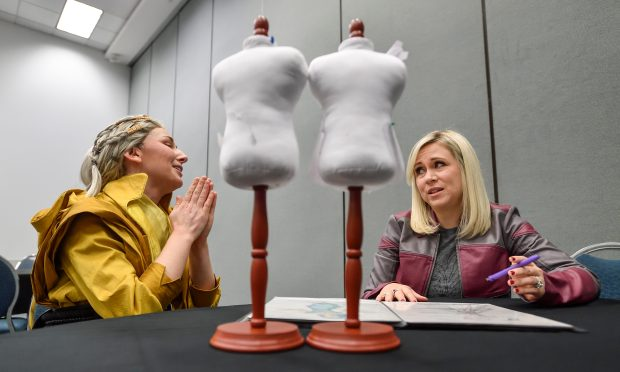 Designer Cynthia Kirkland, dressed as The Ancient One from Dr. Strange, chats with Ashley Eckstein during a portfolio review of Kirkland's designs at WonderCon in Anaheim on Friday, Mar 23, 2018. Eckstein, who started Her Universe, a fashion brand that produces sci-fi themed clothing targeted specifically for girls and women, is looking for designers to participate in a fashion show during ComicCon. (Photo by Jeff Gritchen, Orange County Register/SCNG)