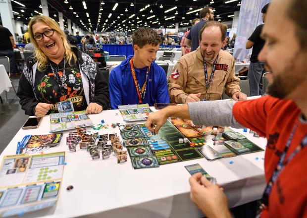 Dawn Phillips, left, her son, Tian Phillips, and husband, Ralph Phillips learn to play Escape from Dulce, a Kickerstarter game developed by team including Craig Sawyer, right, during WonderCon in Anaheim on Friday, Mar 23, 2018. (Photo by Jeff Gritchen, Orange County Register/SCNG)