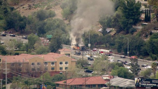 A school bus burns Wednesday afternoon on the westbound 101 Freeway near the Winnetka Avenue off-ramp in Woodland Hills in an image from ABC7's helicopter. (Photo courtesy of ABC7)