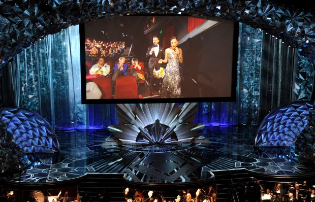 Host Jimmy Kimmel, and Gal Gadot appear on screen via satellite at the Oscars on Sunday, March 4, 2018, at the Dolby Theatre in Los Angeles. Kimmel, Gadot and other celebrities left the Oscars to visit a theater across the street to hand out candy to movie-goers. (Photo by Chris Pizzello/Invision/AP)
