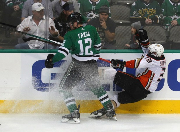 Dallas Stars center Radek Faksa (12) checks Anaheim Ducks right wing Jakob Silfverberg (33) into the boards during the third period of an NHL hockey game Friday, March 9, 2018 in Dallas. (AP Photo/ Richard W. Rodriguez)