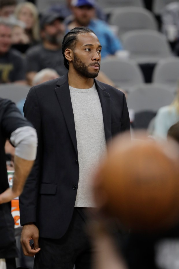 San Antonio Spurs forward Kawhi Leonard, waiting to return from injury, wears street cloths as he watches from the bench during the second half of an NBA basketball game against the New Orleans Pelicans, Wednesday, Feb. 28, 2018, in San Antonio. New Orleans won 121-116. (AP Photo/Eric Gay)