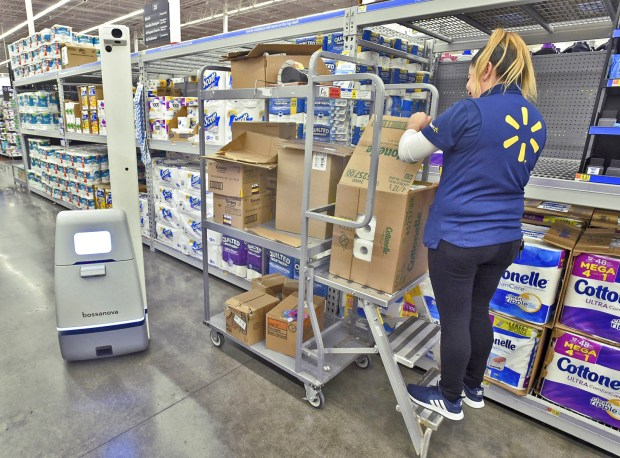 Walmart Associate Sofia Ugalde, right, stocks the shelves as the Bossanova isle-scanning robot senses her and veers into the isle to avoid her ladder in the paper goods isle at Walmart in Burbank on Wednesday, March 21, 2018. Walmart is testing the AI scanning device which it expects to be more efficient at the tedious task of checking inventory on shelves. (Photo by Dan Watson)